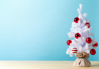 Small white christmas tree with baubles on a blue background