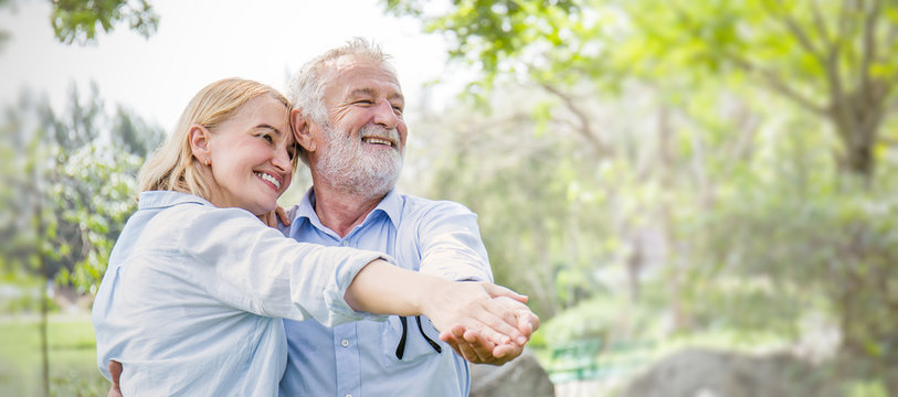 Happy old couple smiling dancing in a park on a sunny day, hoot senior couple relax in the forest spring summer time. Healthcare lifestyle retirement concept banner