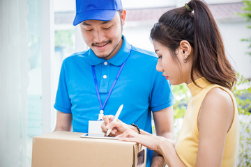 Woman appending receive sign signature after accepting a delivery of boxes from delivery man, sign and receive e-commerce delivery concept