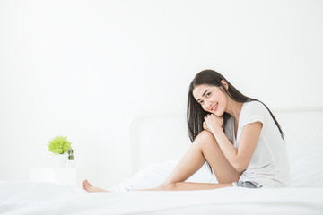 Beautiful young asian sexy woman with attractive smile laying on bed in the morning indoors. Portrait of woman in bedroom relax peaceful concept