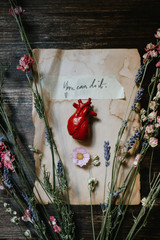 little human heart over a written piece of paper surrounded by flowers