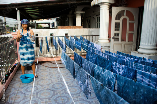 36427d0e8363 Thai women working Indigenous knowledge of thailand tie batik dyeing indigo  color and hanging process dry fabric in the sun at outdoor