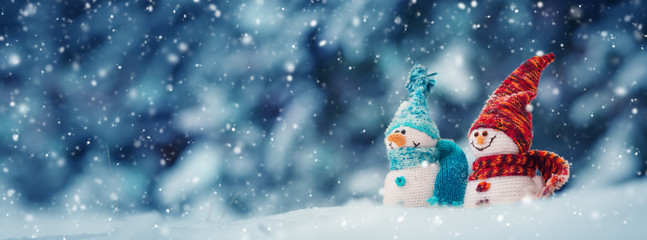little knitted snowmans on soft snow on blue background Wall mural