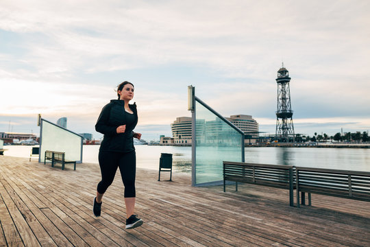Plus size woman running at seaside on a pier.