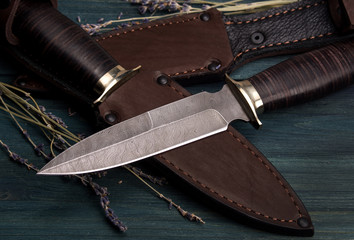 Damascus hunting knives with leather sheath on a vintage wooden background