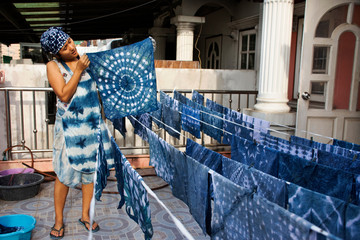Thai women working Indigenous knowledge of thailand tie batik dyeing indigo color and hanging process dry fabric in the sun at outdoor