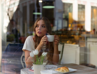 Pretty woman having coffee in cafe alone