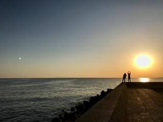 夕焼けの海岸でカップルが写真を撮る
