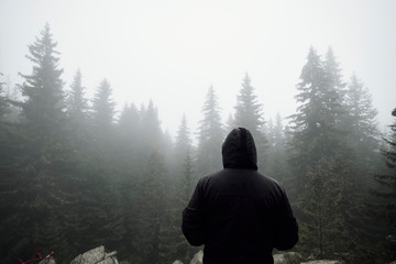 Tourist standing in misty woods