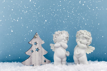 two Christmas baby angels statuettes on snow with wooden Christmas tree and copy space