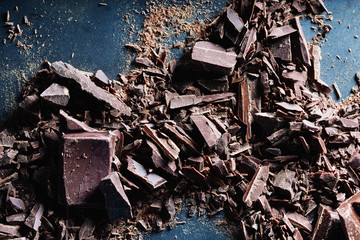 Chocolate. Shards of chopped chocolate on metal background.