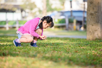 Little girl discovering and collecting wild berries on grass