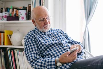 Senior man using his phone relaxed at home.