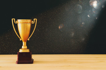 low key image of gold trophy over wooden table and dark background, with abstract glitter lights.