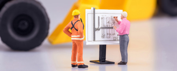 Miniature engineering people and architecture working on construction drawing in cover banner size. Elegant Design for industrial and construction concept.
