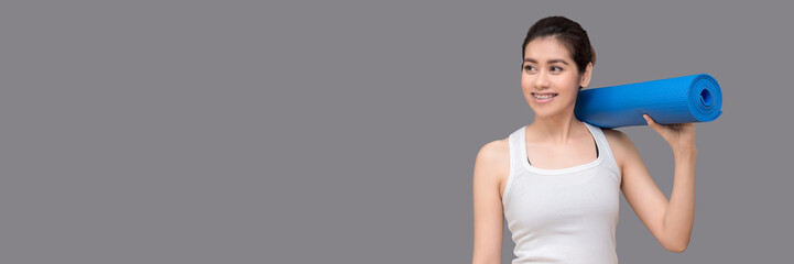 Young asian woman holding her yoga mat and charming smile while go to practice yoga exercise at the yoga sport gym.Photo design in banner cover size with copy space for add text.