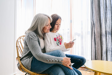 Grandmother and her grandchild using phone at home.