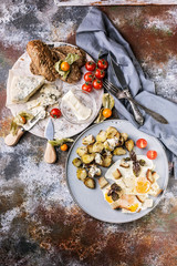 Fried eggs with croutons, sprouts, butter, cheese and a baguette with pumpkin seeds, close-up delicious breakfast concept. Vertical shot