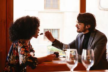 Lovers eating dessert in restaurant.