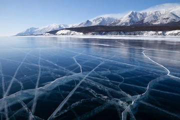 Beautiful cracks pattern on glossy smooth surface of frozen lake Baikal, scenic winter landscape or background with blue ice open space and mountains covered with snow