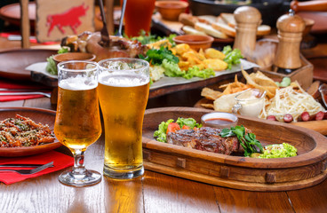 Beer table in the pub. Hot steak with sauce and vegetables.
