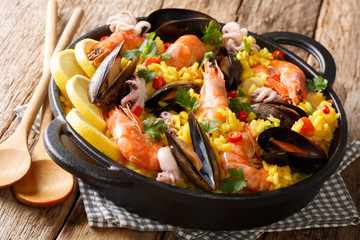 Spanish spicy paella seafood with king prawns, mussels, fish, and baby octopus closeup on wooden background. horizontal