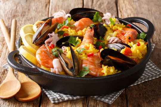 Homemade freshly prepared paella with king prawns, mussels, fish, and baby octopus served in a pan on a wooden table. horizontal