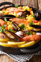 Closeup of traditional Spanish paella with seafood in a pan. vertical