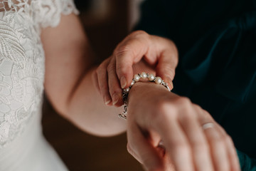 Mother of the Bride Putting on Bracelet on Bride