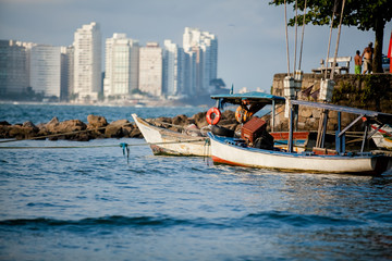 small fishing boats in the blue sea of ​​Asturias beach in Guarujá in Brazil