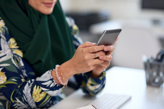 Anonymous woman in hijab using mobile phone