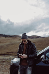 Stylish Young Man standing in front of his Car and Texting