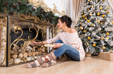 1 white girl in jeans and pink sweater by the fireplace and Christmas tree