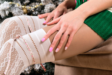 women's legs in white fishnet stockings and women's hands with pink manicure