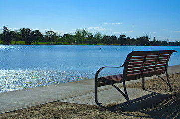 Empty bench facing lake with blue sky and blue water