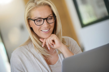 Portrait of blond woman with eyeglasses working on laptop