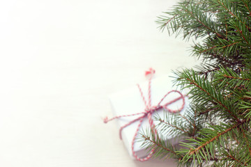 place for Christmas greetings/ branch of an evergreen tree on a blurred background with outlines of a top view gift