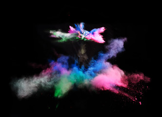 Multi Colored forms of powder paint and flour combined  together explode in front of a black background to give off fantastic  multi colored explosions.