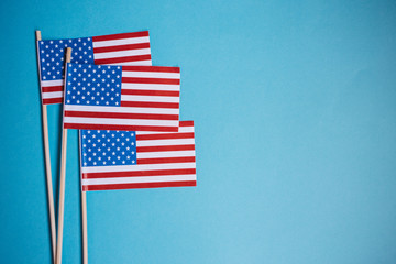 Miniature paper flag USA. American Flag on blue background.