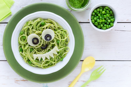 Fun food for kids - cute smiling face of green spaghetti monster served in a white bowl with eyes made of cheese and olives. Healthy vegetarian eating for children