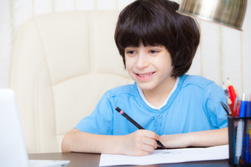 smiling child doing homework with computer