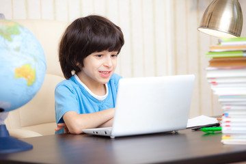 smiling boy looking at a computer monitor