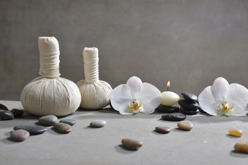 Two orchid with black stones, herbal ball,,candle on gray background