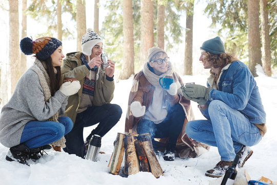 Full length portrait of four young people camping in winter forest sitting in circle round fire and chatting while drinking hot cocoa