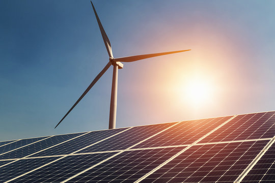 concept clean energy power in nature. solar panel and wind turbine with sunlight blue sky background