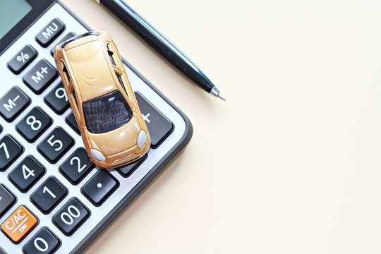 Business, finance, saving money, banking or car loan concept : Top view or flat lay of miniature car model, calculator and pen on office desk table with copy space ready for adding or mock up