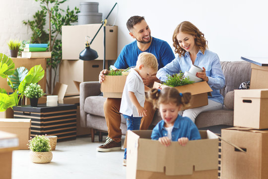 happy family mother father and children move to new apartment and unpack boxes.