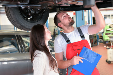 car mechanic and customer in a workshop - consulting and customer service // Kundin und Monteur in einer Autowerkstatt