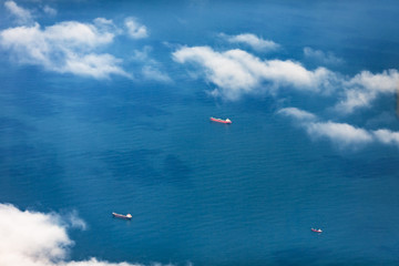 Aerial view through a veil of clouds on three cargoships floating in ocean waters.