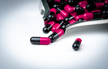 Pink-black capsule pills on drug tray. Antibiotics drug resistance. Global healthcare. Antimicrobial capsule pills. Pharmacy background. Antibiotic drug use with reasonable. Pharmaceutical industry.